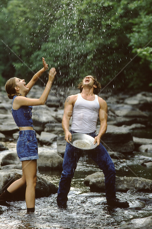 couple enjoying time together splashing in a stream