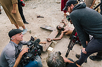 """MATERA, ITALY -6 OCTOBER 2019:  Yvan Sagnet (34, center), a political activist and former exploited tomato farmer, is seen here performing Jesus Christ before filming the scene of the crucifixion in """"The New Gospel"""", a film by Swiss theatre director Milo Rau, in Matera, Italy, on October 6th 2019.<br /> <br /> Theatre Director Milo Rau filmed the Passion of the Christ  under the title """"The New Gospel"""" with a cast of refugees, activists and former actors from Pasolini and Mel Gibson's films.<br /> <br /> The role of Jesus is performed by Yvan Sagnet, a Political activist born in Cameroon and who worked on a tomato farm when in 2011 he revolted against the system of exploitation and led the first farm workers' strike in southern Italy. In a series of public shoots in the European Capital of Culture Matera, Jesus will proclaimed the Word of God, was crucified (October 6th 2019) and finally rose from the dead in Rome, the capital of Catholic Christianity and seat of one of the most xenophobic governments in Europe (October 10th 2019).<br />  <br /> Parallel to the film, the humanistic message of the New Testament was transformed into the present: at the beginning of September, the campaign """"Rivolta della Dignità"""" (Revolt of Dignity), which demanded fair working and living conditions     for refugees, global freedom of travel and civil rights for all, started with a march from the southern Italian refugee camps. """"It's about putting Jesus on his feet,"""" director Milo Rau said. Led by Jesus actor Yvan Sagnet, the campaign fights for the rights of migrants who came to Europe via the Mediterranean to be enslaved by the Mafia in the tomato fields of southern Italy and to live in ghettos under inhumane conditions. The campaign and the film thus create a """"New Gospel"""" for the 21st century, a manifesto of solidarity with the poorest, a revolt for a more just and humane world."""