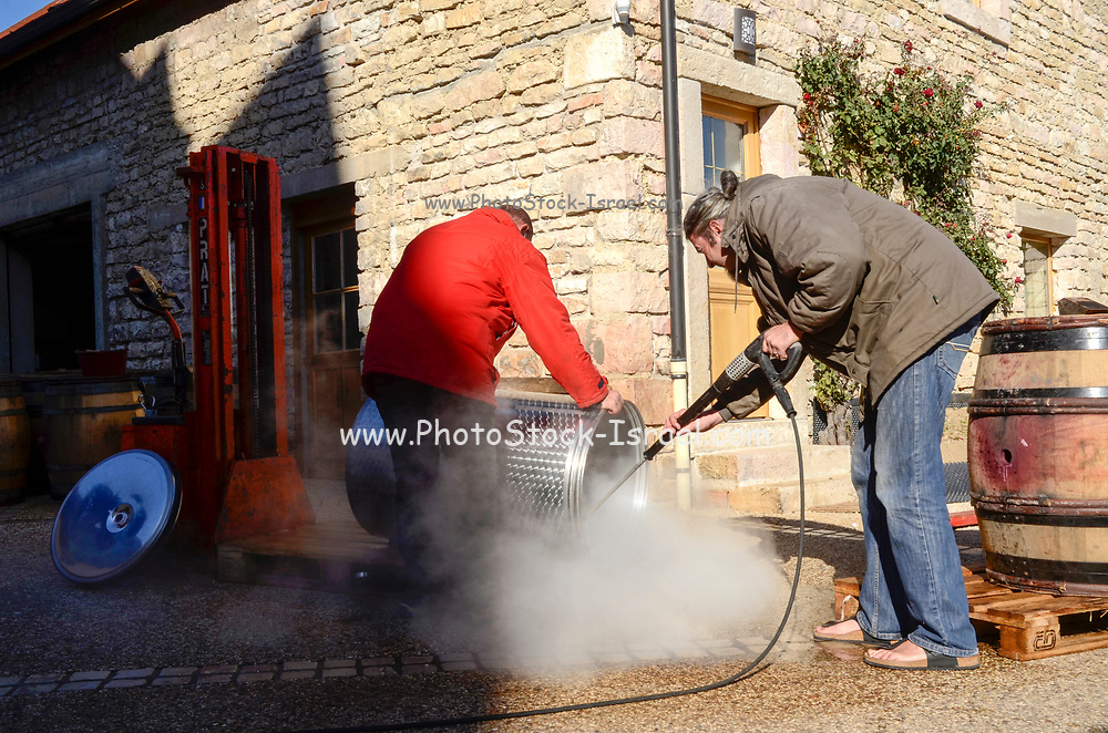 Men cleaning barrels with a water jet. Photographed in France