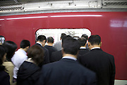 Japanese business commuters entering a train