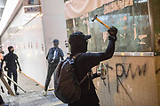HONG KONG: 13 October 2019 <br /> A protester vandalises an MTR metro station in the Sham Shui Po district of Hong Kong earlier this evening. Running battles between protesters and riot police continued today as demonstrators move into their 19th consecutive week of protests in Hong Kong. The movement's aim, which started on June 1st, originally wanted to get rid of a controversial extradition bill which has since been removed, however the protests have formed into a wider fight against police brutality and the ability to wear a mask without fear of arrest.<br /> Rick Findler / Story Picture Agency