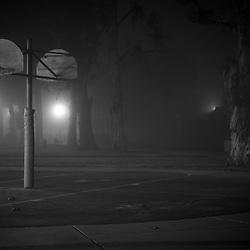Basketball hoops in a suburban park on a foggy night. Irvine, CA.