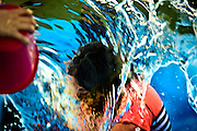 Kaitlin Mote, 12, is overtaken by a wave of water tossed by a friend during a National Night Out Block Party at Providence within Knickerbocker Park combining fun and education to help promote community safety on Tuesday, August 4, 2015.  L.E. Baskow