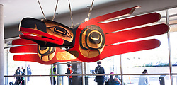 """Hugging the World"", a red cedar carving done in Northwest Coast style hangs in the domestic terminal at Vancouver International Airport, in Vancouver, British Columbia. The artwork, by Robert Davidson, has two large dance masks of an Eagle and Raven that are mounted back to back. Eagles and Ravens are important in Haida spiritual beliefs and social structure."