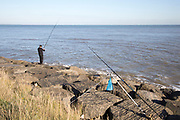 Man sea fishing standing on coastal defence rock armour, Bawdsey, Hollesley Bay, Suffolk, England, UK