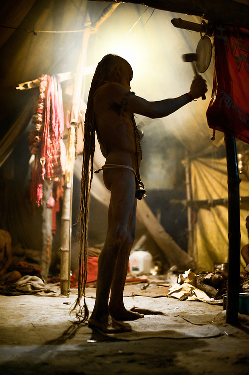 A Naga Sadhu going through his evening prayer routine during the Kumbh Mela, Juna Akhara, Haridwar, 2010. Naga Sadhus belong to the Shaiva sect, they have matted locks of hair and their bodies are covered in ashes like Lord Shiva.<br />