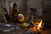 Women cooking chapattis on an open fire, India.