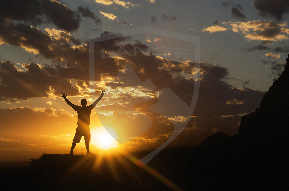 nature scenery and inspirational concepts: silhouette of man celebrating the dramatic sunset sky, standing, arms spread wide, sandia mountains, albuquerque, new mexico, usa, horizontal, copy space,