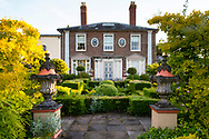 Stone urns decorated withram's heads, Taxus baccata and Buxus topiary in the Howdah Court in front of the house at The Laskett Gardens, Much Birch, Herefordshire, UK