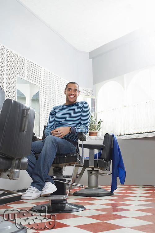 Man sitting in barbers shop portrait
