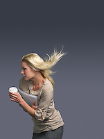 Woman with hair blowing holding coffee facing into wind
