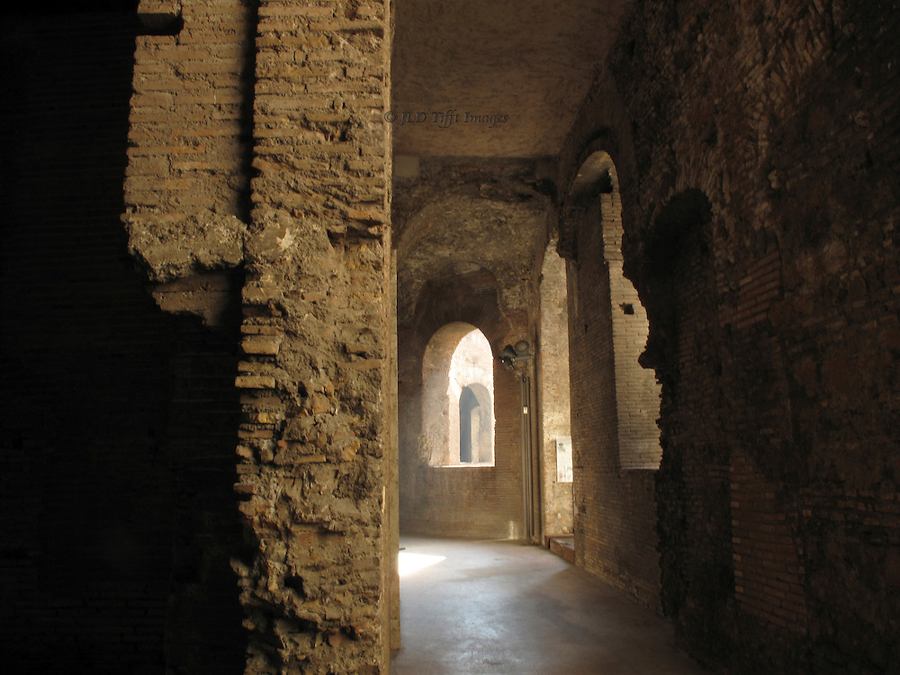 Interior of a curving corridor along an upper floor in Trajan's Markets, showing arched windows and brickwork detail, with more windows seen through the nearest one.  Gentle daylight illuminates the floor and wall stumps.