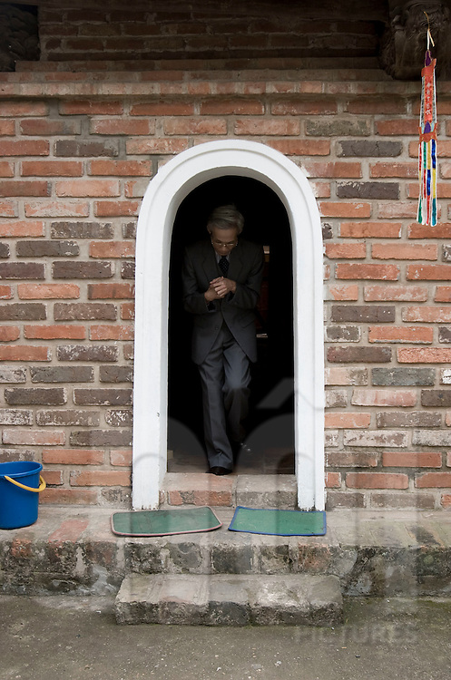An old vietnamese man wearing a suit goes through a tiny arch in a pagoda. Hanoi, Vietnam, Asia