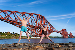 North Queensferry, Scotland, UK. 26 May 2020. Kenny McAlpine and Jenny Waring from Fife Wild Swimmers group make the most of the warm sunshine and an exercise escape from the Covid-19 lockdown and jump into the Firth of Forth at North Queensferry with the Forth Bridge as a dramatic backdrop. Iain Masterton/Alamy Live News