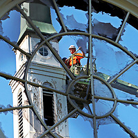 A worker is seen through the shattered stained glass of the Church of Jesus Christ of Latter-Day Saints at 2 Longfellow Park. He is surveying ways to save the steeple after sunday's fire devastated the church.