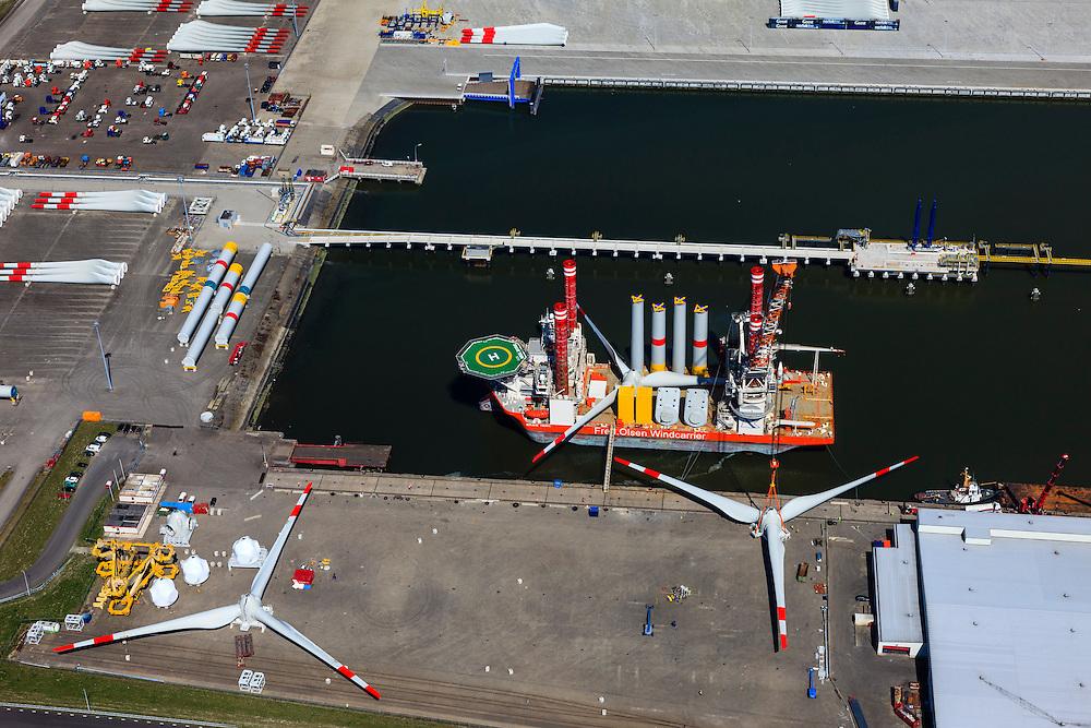 Nederland, Groningen, Eemshaven, 01-05-2013; de Julianahaven, opslag en assemblage van onderdelen van offshore windturbines, zoals wieken (rotorbladen), masten, turbines. Op de  windcarrier met helikopterdek de onderdelen van windmolens. Een hijskraan hijst een gemonteerd  wiekenblok omhoog..De firma Fred. Olsen Windcarrier is verantwoordelijk voor transport, installatie en onderhoud van offshore wind parken..Port of Eemshaven: storage and assembly of components for offshore wind turbines in the Julianahaven at Eemshaven. .Fred. Olsen Windcarrier company provides innovative and tailored services for the transport, installation, and maintenance of offshore wind parks, such as wings (blades), masts, turbines. On the wind carrier with helicopter deck the parts of a windmill. A crane lifts mounted wings..luchtfoto (toeslag op standard tarieven).aerial photo (additional fee required).copyright foto/photo Siebe Swart
