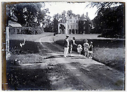 family on the lawn to their mansion 1900s
