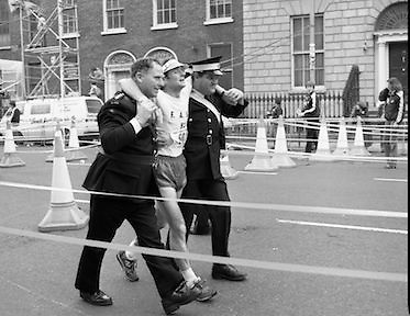Finish of Dublin City Marathon .25/10/1982  Radio 2, Dublin City Marathon..1982.25.10.1982.10.25.1982.25th October 1982..The Radio 2 sponsored Dublin City Marathon finish at St Stephens Green Dublin..The overall winners were:Men, Gerry Kiernan,Listowel, Kerry. Women, Debbie Mueller,U.S.A. and the first wheelchair competitor Michael O'Rourke.The end in sight,this competitor gets the welcome assistance of the St John's Ambulance crew.