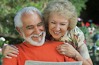 Senior couple reading newspaper in garden