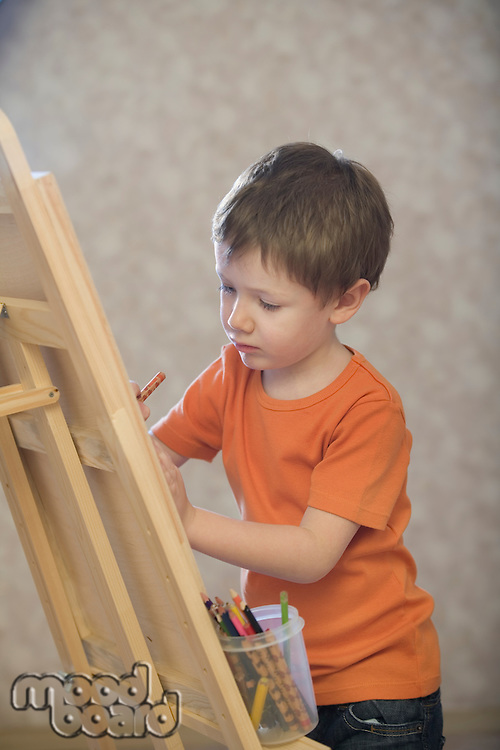 A young boy drawing onto a canvas  with a pot of coloured pencils stood on the ledge of the canvas