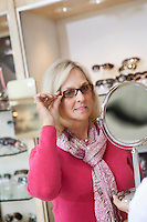 Senior woman trying glasses while looking into hand mirror in store