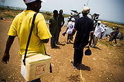 A health worker walks around the ferry terminal in Makango, northern Ghana, to find children to vaccinate during a national polio immunization exercise on Thursday March 26, 2009.