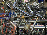 close up of the handlebars of a cluster parked bicycles