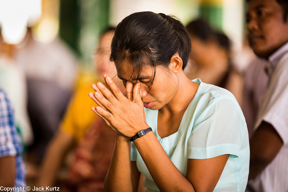 15 JUNE 2013 - YANGON, MYANMAR:  Women pray at Shwedagon Pagoda. The Shwedagon Pagoda is officially known as Shwedagon Zedi Daw and is also called the Great Dagon Pagoda or the Golden Pagoda. It is a 99 metres (325 ft) tall pagoda and stupa located in Yangon, Burma. The pagoda lies to the west of on Singuttara Hill, and dominates the skyline of the city. It is the most sacred Buddhist pagoda in Myanmar and contains relics of the past four Buddhas enshrined: the staff of Kakusandha, the water filter of Koṇāgamana, a piece of the robe of Kassapa and eight strands of hair fromGautama, the historical Buddha. The pagoda was built between the 6th and 10th centuries by the Mon people, who used to dominate the area around what is now Yangon (Rangoon). The pagoda has been renovated numerous times through the centuries. Millions of Burmese and tens of thousands of tourists visit the pagoda every year, which is the most visited site in Yangon.  PHOTO BY JACK KURTZ