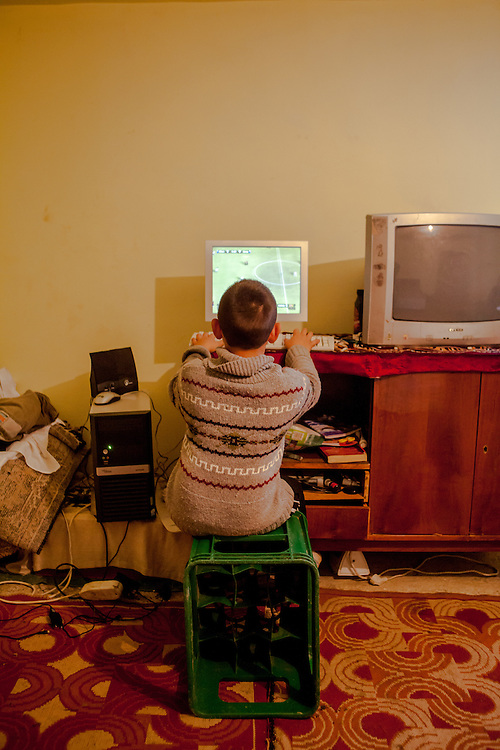Son Alberto (8) playing a football game on his home PC sitting on a case instead of a chair.