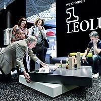 Nederland,Amsterdam ,30 september 2008..Vertegenwoordiger van meubelstand LEOLUX demonstreert enkele bezoekers tijdens de Woonbeurs 2008 een salontafel .