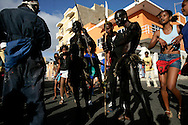 "In Carnival parades in Mindelo, attempts to recover the tradition of ""mandigas"" groups are made. These were members of African groups also used as slaves in Cape Verde. They rumble the streets chaotically playing with the audience and covered with oil or mud. They are generally from the poorer strata of population."