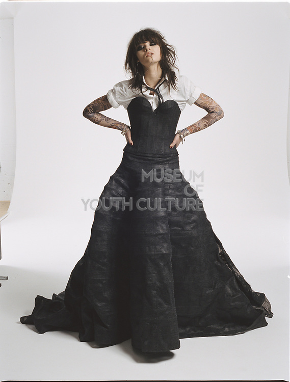 Young woman wearing a black evening gown with white short sleeved shirt posing with hands on hips and head tilted back.