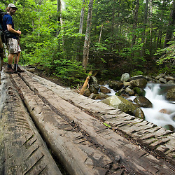A hiker on a bridge over Gorge Brook on Mount Moosilauke in New Hampshire's White Mountain National Forest. (MR)