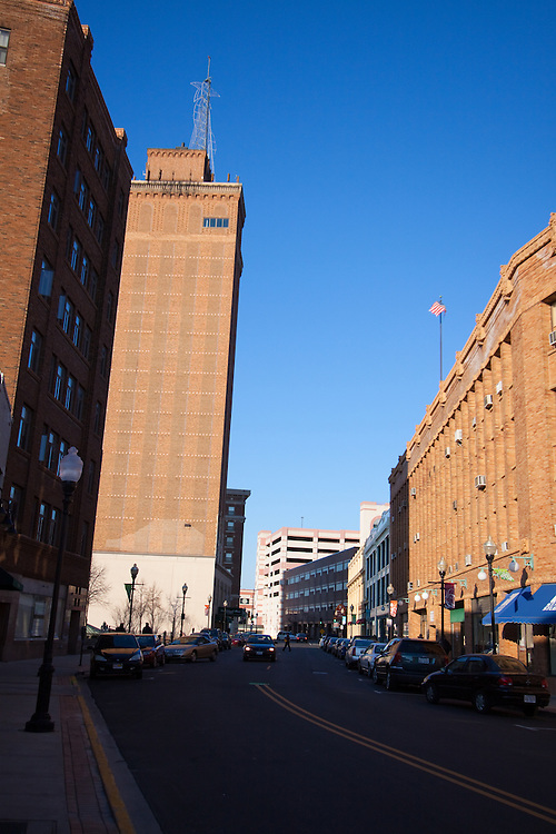 S. Stolp Ave, in downtown Aurora, IL as the sun sets. To the left is the historic Keystone Building, and standing tall behind is the Leland Tower.