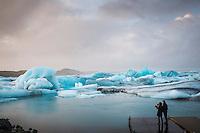 Tourists by Jökulsárlón glacial lagoon, southeast Iceland. Moody sky over blue icebergs.