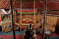 Mongolia. Ulaanbaatar. Palace of Bogdo Khan (last king of Mongolia), The royal yurt (Ger) in the winter palace  Oulan Bator Ulan Baatar   Mongolia      /  Interieure de la yourte (ger) souveraine du dernier theocrate [Debut du XXème].  /  Lors de ses deplacements, le souverain utilisait cette somptueuse yourte, richement sculptee et decoree aux tons de rouge et d'or, avec son mobilier precieux et sa vaisselle d'argent. A gauche du lit, un autel portatif avec des statuettes en bronze dore à l'or; à droite son trône de campagne. L'exterieur de la yourte est recouverte de peaux de lynx des neiges, animal aujourd'hui protege. (Palais-musee du BOGDO GEGEN, OULAN BATOR   /  /49    L0006044  /  P0002654