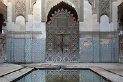 Low angle view of main door to the central patio reflecting in pool in foreground, Sahrij Medersa, (Medersa des Andalous), 1321, Fez, Morocco, pictured on February 23, 2009 in the morning. The Sahrij Medersa takes its name from the pool in its courtyard, (sahrij means basin). Green and white minarets crown the theological school founded by Merinid sultan Abou al-Hassan and attached to the Al-Andalous mosque.  It is decorated with ornate  dark cedar panels (mashrabiya), decorated tiles (zellij), marble pavings and intricate plasterwork. Fez, Morocco's second largest city, and one of the four imperial cities, was founded in 789 by Idris I on the banks of the River Fez. The oldest university in the world is here and the city is still the Moroccan cultural and spiritual centre. Fez has three sectors: the oldest part, the walled city of Fes-el-Bali, houses Morocco's largest medina and is a UNESCO World Heritage Site;  Fes-el-Jedid was founded in 1244 as a new capital by the Merenid dynasty, and contains the Mellah, or Jewish quarter; Ville Nouvelle was built by the French who took over most of Morocco in 1912 and transferred the capital to Rabat. Picture by Manuel Cohen.