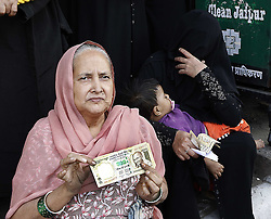 November 12, 2016 - Jaipur, Rajasthan, India - Indian muslim women show old currency notes as they waiting in a queue  to deposit and exchange discontinued Rs 500,1000 currency notes outside a bank in Jaipur, India, Saturday, Nov. 12, 2016. Long queues have grown longer, scuffles have broken out and chaotic scenes are being seen across India as millions of people waited to change old currency notes that have become worthless after the government's demonetized high value bills. (Photo By Vishal Bhatnagar/NurPhoto) (Credit Image: © Vishal Bhatnagar/NurPhoto via ZUMA Press)