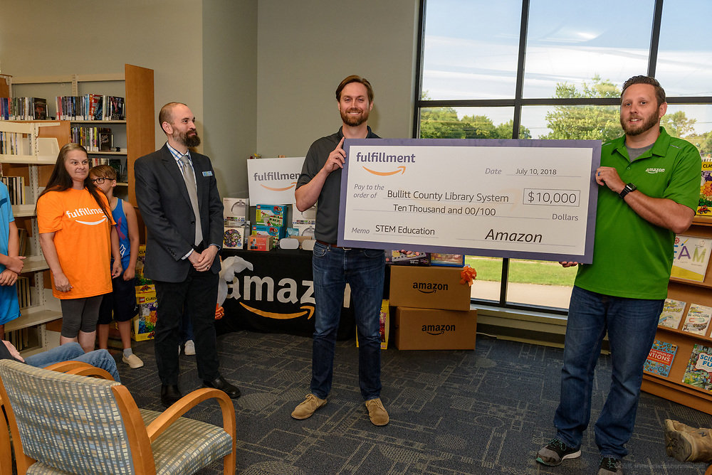 Bullitt County Public Library Director Joe Schweiss, left, looks on as Amazon leaders Matt Harney and Brett Gorin present a donation of $10,000 in new technology to support Bullitt County Library's STEM and STEAM programs for students in the Bullitt County School District Tuesday, July 10, 2018 at the Ridgway Memorial Library in Shepherdsville, Ky. The donation will enhance the library's current Digital Tech and Makerspace Lab programs and ignite more students to take advantage of STEM education outside of the classrooms and included Oculus Go headsets, a Cubelets classroom, and several sets of LEGOs that will increase the lab's ability to help students learn and explore STEM. (Photo by Brian Bohannon)