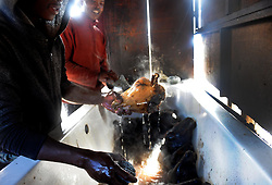 Cape Town-180906 Avuya Msongwelwa and Sinoxolo Mcetywa cleaning the Sheep head before thoroughly scrubbed and rinsed well to remove all hairs. The Sheep head also know as Smiley is very popular in the township it used to be cooked only if there was traditional cremony nowadays there are many places that clean and sell this delicacy,cooked or uncooked Sheep head cost R70 and half R35 Pictures Ayanda Ndamane/African/news/agency ANA