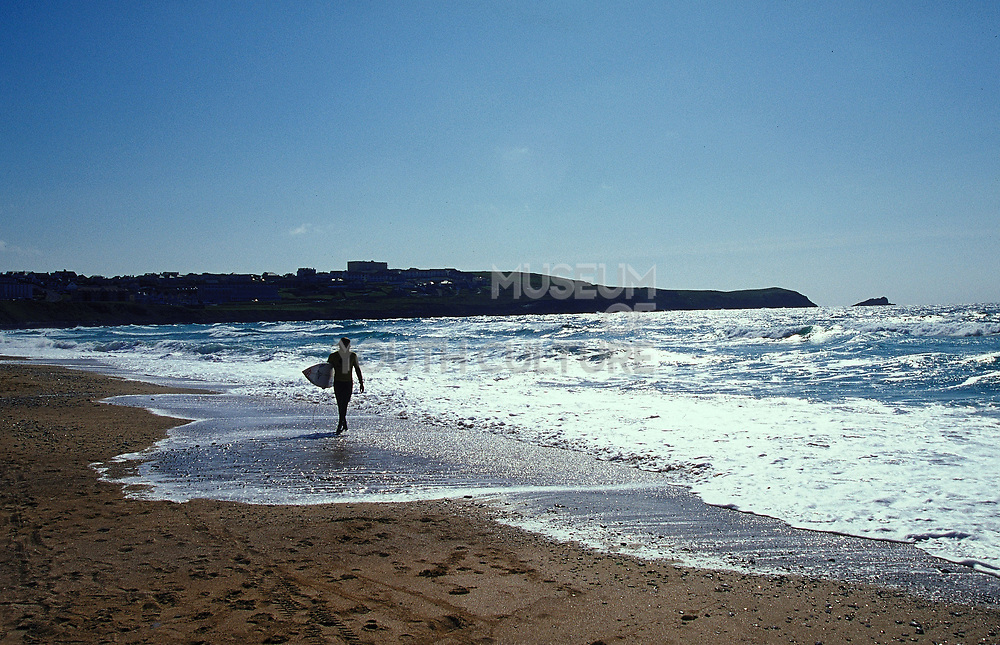 Surfer with surf board walking along Fistral beach Newquay UK May 2002
