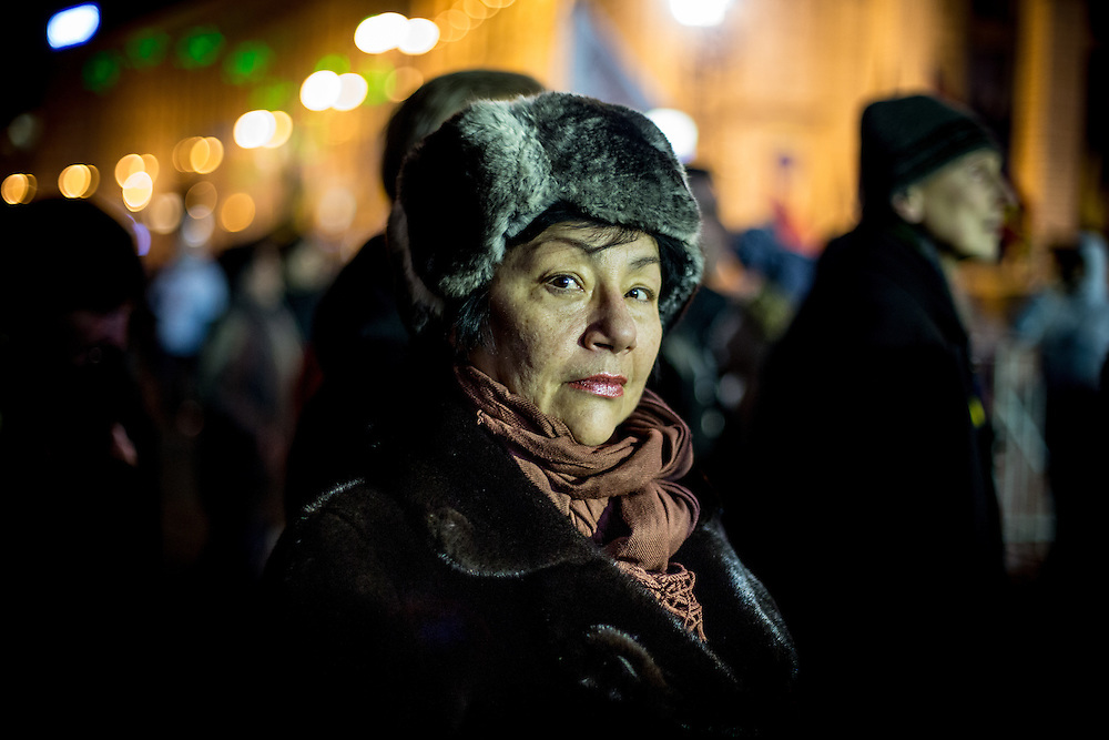 A woman listens to the speeches, on the Independance Square, at night.
