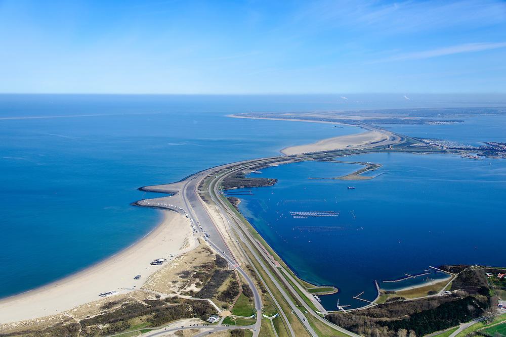 Nederland, Zeeland, Gemeente Schouwen-Duiveland, 01-04-2016; Brouwersdam, onderdeel van de Deltawerken, tussen Schouwen-Duiveland en Goeree (aan de horizon). Na het afsluiten van de zeearm Grevelingen is het Grevelingenmeer ontstaan, rechts van de dam, het grootste zoutwatermeer van West-Europa. Om de kwaliteit van het water in het meer te garanderen is er in de dam een inlaatwerk voor zout zeewater aangebracht (midden). Links de Noordzee, in het midden Middelplaat en recreatiecentrum en vakantiepark Port Zelande. <br /> <br /> Brouwers dam, part of the Delta Works, between Goeree and Schouwen-Duiveland (on the horizon). Closing the estuary resulted in the Grevelingen lake, the largest saltwater lake in Western Europe.<br /> <br /> luchtfoto (toeslag op standard tarieven);<br /> aerial photo (additional fee required);<br /> copyright foto/photo Siebe Swart