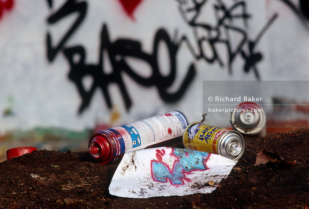 Abandoned aerosol spray cans lie in soil after a graffiti gang's overnight vandalism visit in Notting Hill, West London.  We see the cans having been emptied of their contents, in the soil next to the wall that has been covered with tags and graffiti art, the drawings of which have been sketched on a sheet of paper.