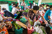 15 JUNE 2013 - YANGON, MYANMAR:  A water vendor works on the Yangon Circular Train. The Yangon Circular Railway is the local commuter rail network that serves the Yangon metropolitan area. Operated by Myanmar Railways, the 45.9-kilometre (28.5mi) 39-station loop system connects satellite towns and suburban areas to the city. The railway has about 200 coaches, runs 20 times and sells 100,000 to 150,000 tickets daily. The loop, which takes about three hours to complete, is a popular for tourists to see a cross section of life in Yangon. The trains from 3:45 am to 10:15 pm daily. The cost of a ticket for a distance of 15 miles is ten kyats (~nine US cents), and that for over 15 miles is twenty kyats (~18 US cents). Foreigners pay 1 USD (Kyat not accepted), regardless of the length of the journey.     PHOTO BY JACK KURTZ