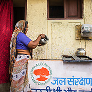 CAPTION: A woman pours water into her cement storage tank, which was set up by TARU. 16 households in Narwal Kankad signed up for this pilot project. LOCATION: Narwal Kankad, Indore, Madhya Pradesh, India. INDIVIDUAL(S) PHOTOGRAPHED: Unknown.
