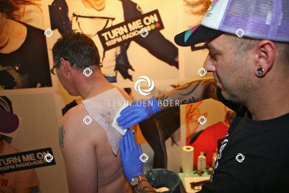 HILVERSUM - Bij radio 538 was het een bijzondere nacht, de uitzending 53N8CLUB had namelijk een bijzondere fan in de studio die de portretten van de DJ's op zijn rug liet tatoeeren door Jan's Tattoo Studio Zaltbommel. Met op de foto Jan Sidiropoulos en Gerard Schalken. FOTO LEVIN DEN BOER / PERSFOTO.NU