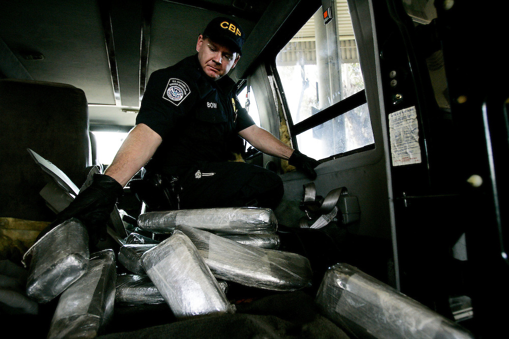 Customs and Border Protection agent Ian Bow pulls out bricks of Marijuana from a van seized at the U.S. Port of Entry in San Ysidro, Calif.  The drugs were concealed throughout the van behind wall  paneling and in a chamber in the gas tank.