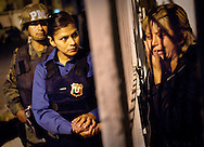 Ciudad Juaraz Municipal police officer Noeme Martinez, center comforts Maria Campos, right, in the driveway of her house after learning that her husband was found brutally murdered. The war on drugs rages across Mexico claiming thousands of lives. (photo by Sarah L. Voisin/The Washington Post)