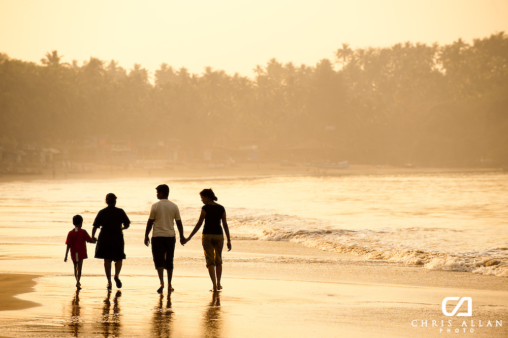 A family walking at sunset along the Goan Beach, Goa, India